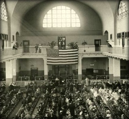 Detail from photo of immigrants seated on long benches, Main Hall, U.S. Immigration Station, date unknown; New York Public Library Digital Collection