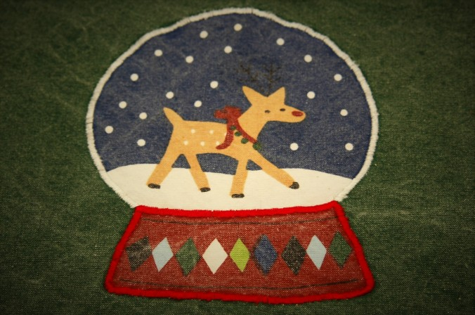 Detail of reindeer in snow globe on denim Christmas placemat